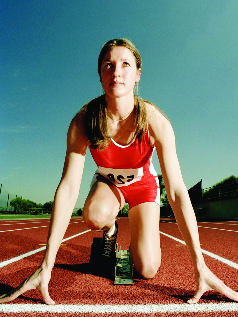 ca. 2003 --- Runner Crouching at Starting Line --- Image by © Royalty-Free/Corbis