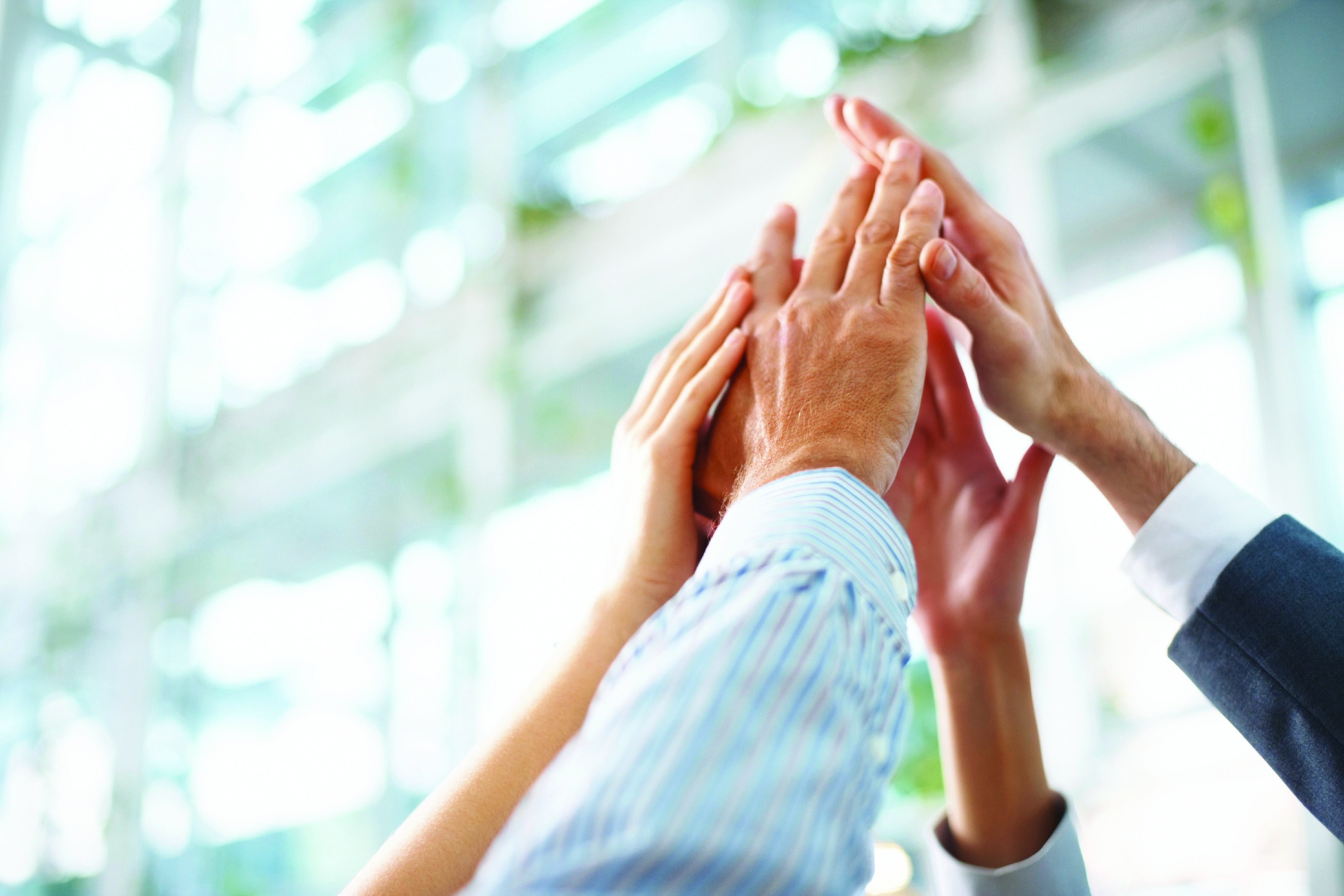 Cropped image of business people hands giving high five